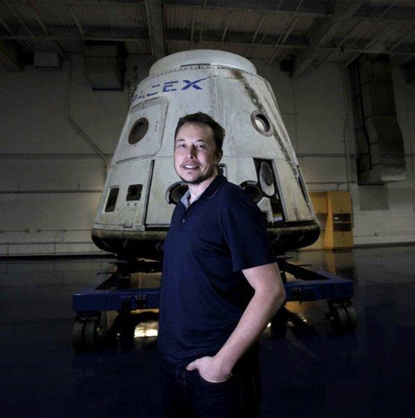 """Elon Musk devant sa première capsule récupérée. Notez le """"scratch"""" de la rentrée en orbite sur la droite !"""
